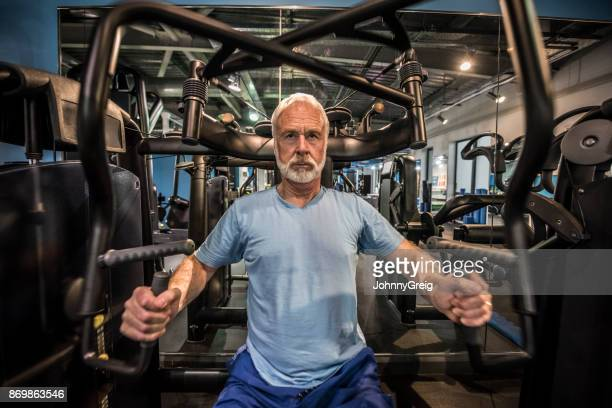 Serious senior man with grey hair and beard using weights equipment in the gym