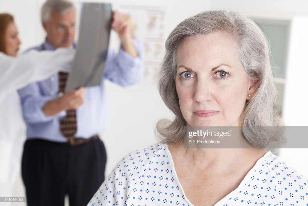 Serious Senior Patient in Doctor Office While Physicians Examine X-Ray : Bildbanksbilder