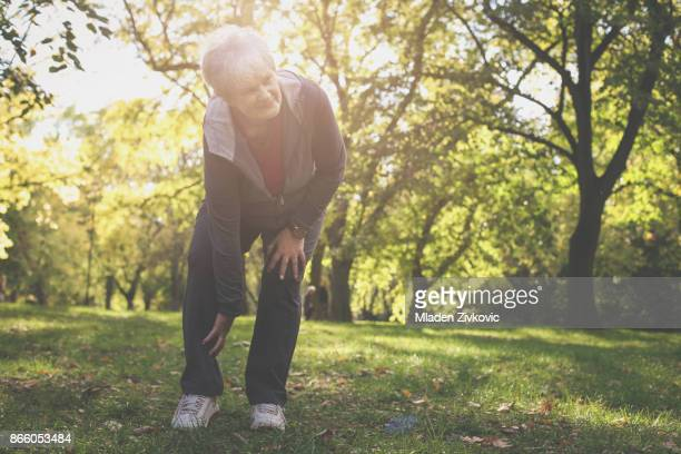 serious senior woman having pain in knee after exercise. - older woman legs stock photos and pictures