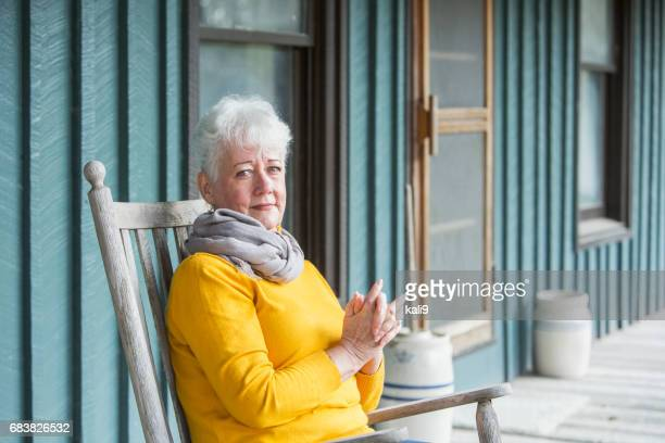 serious senior woman sitting in rocking chair - rocking chair stock pictures, royalty-free photos & images