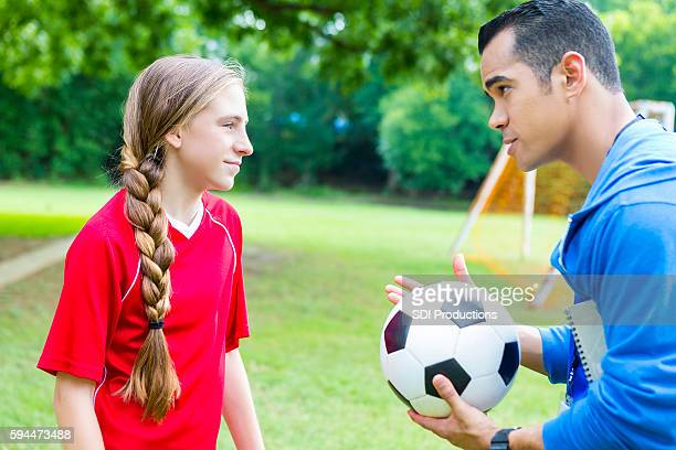 Serious soccer coach talks with player