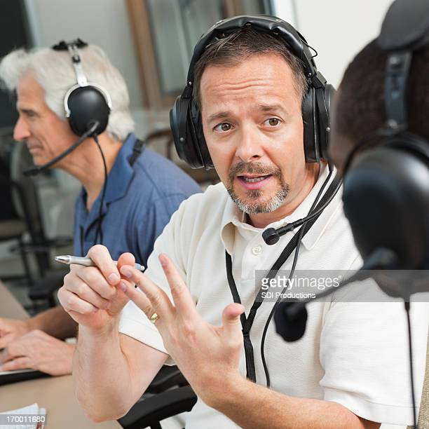 serious sports commentator discussing game in the press box - commentator stock pictures, royalty-free photos & images