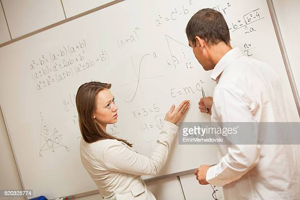 Serious student listening teacher during physics class.