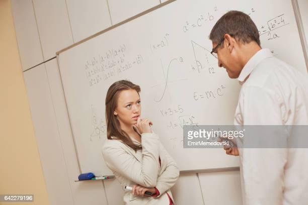 Serieuze student luisteren leraar tijdens de natuurkunde les