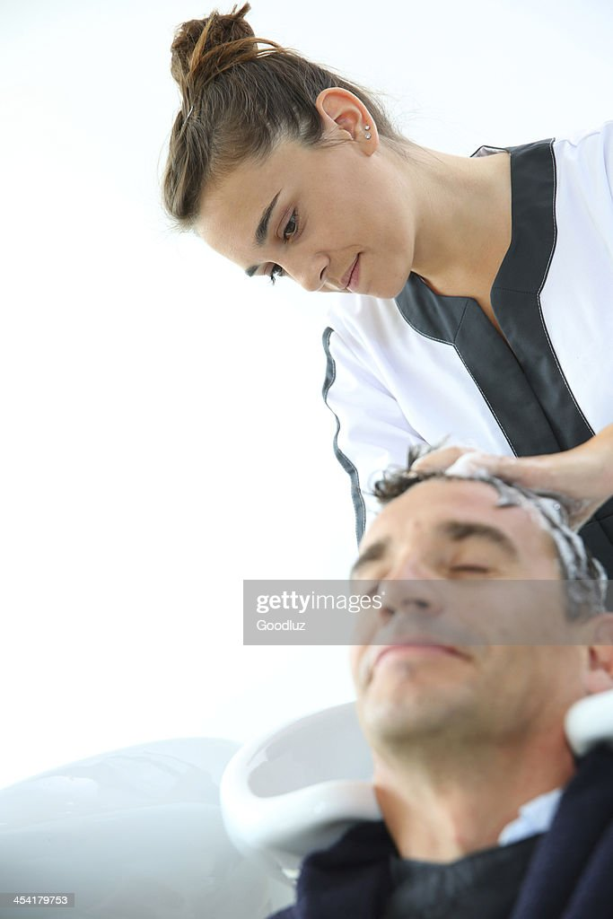 Serious studiant doing shampoo in hair salon : Stock Photo
