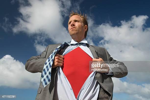 Serious Superhero Businessman Standing Outdoors against Bright Sky