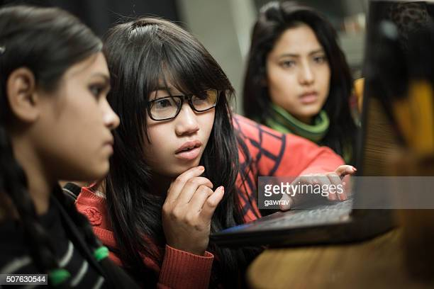 Serious teenage Asian girls of different ethnicity using laptop together.