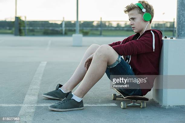 serious teenage boy outdoors on skateboard listening to music - ショートパンツ ストックフォトと画像
