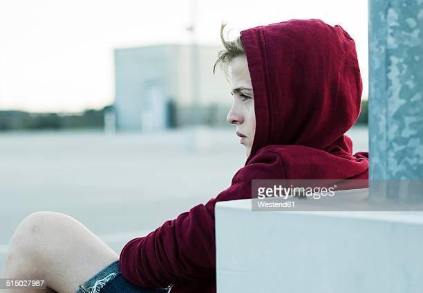 Serious teenage boy outdoors wearing hooded jacket