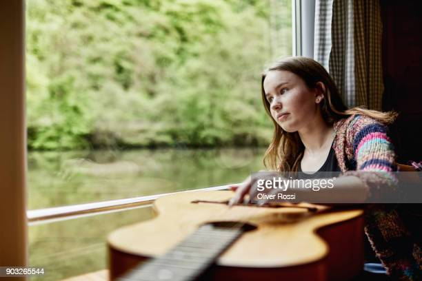 Serious teenage girl with guitar on a houseboat