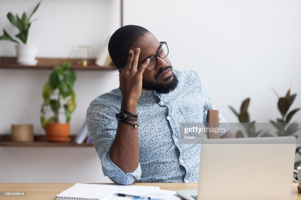 Serious thoughtful african businessman sitting at desk : Stock Photo
