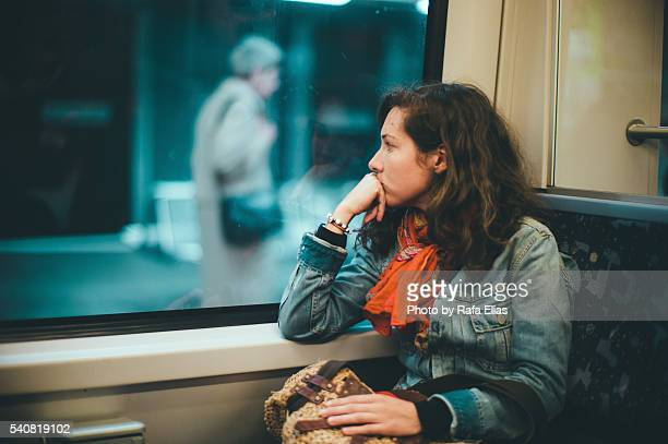 serious thoughtful woman in train car - 列車の車両 ストックフォトと画像