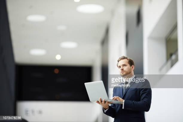 Serious thoughtful young bearded businessman in formal jacket and tie standing in modern office lobby and holding laptop while editing data on laptop and looking away
