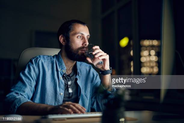 serious thoughtful young bearded man in casual shirt sitting in night office and drinking water while using computer - one man only stock pictures, royalty-free photos & images