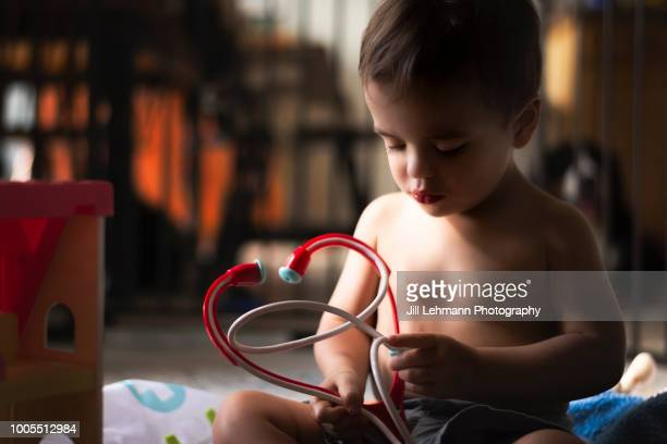 Serious Toddler Is Sick and Plays Shirtless with Toy Stethoscope
