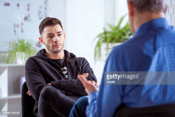 serious university student listening to therapist - talking stock pictures, royalty-free photos & images