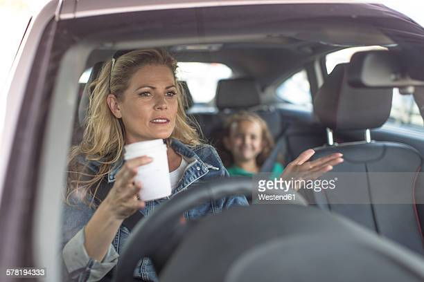 Serious woman and girl in car