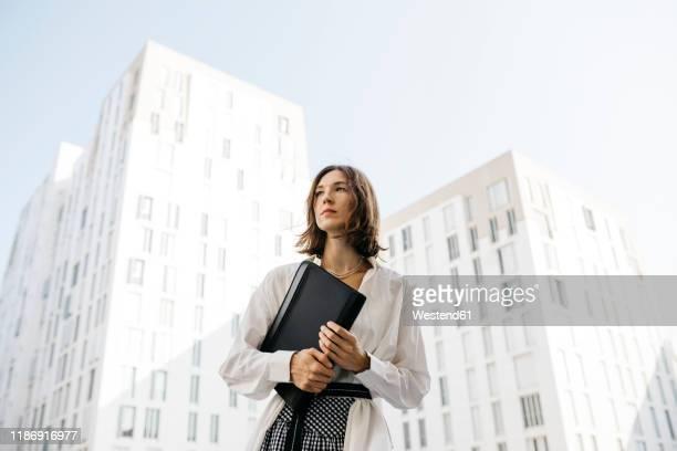 serious woman carryiing folder in the city - vestimenta de negocios fotografías e imágenes de stock