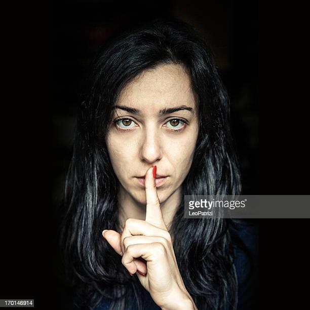 grave mulher com o dedo nos lábios - silêncio - fotografias e filmes do acervo