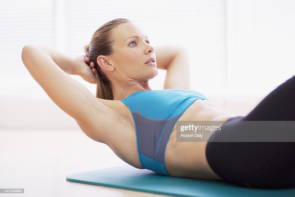 Serious woman in sports bra doing sit-ups on exercise mat : Stock Photo