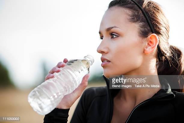 Serious woman in sportswear drinking water