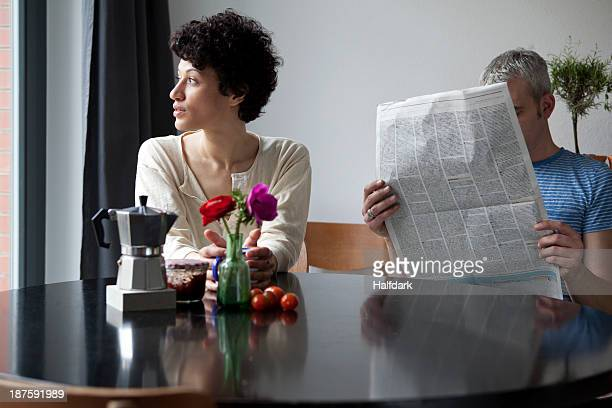 a serious woman looking out a window while her boyfriend hides behind a newspaper - heterosexuelles paar stock-fotos und bilder
