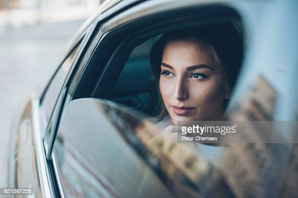 serious woman looking out of a car window - ricchezza foto e immagini stock