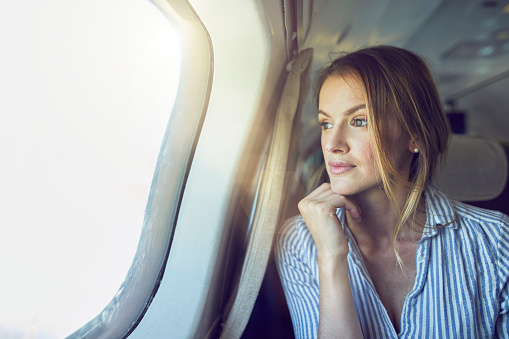 Serious woman looking out of airplane window - gettyimageskorea