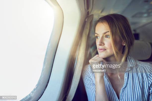 serious woman looking out of airplane window - geschäftsreise stock-fotos und bilder