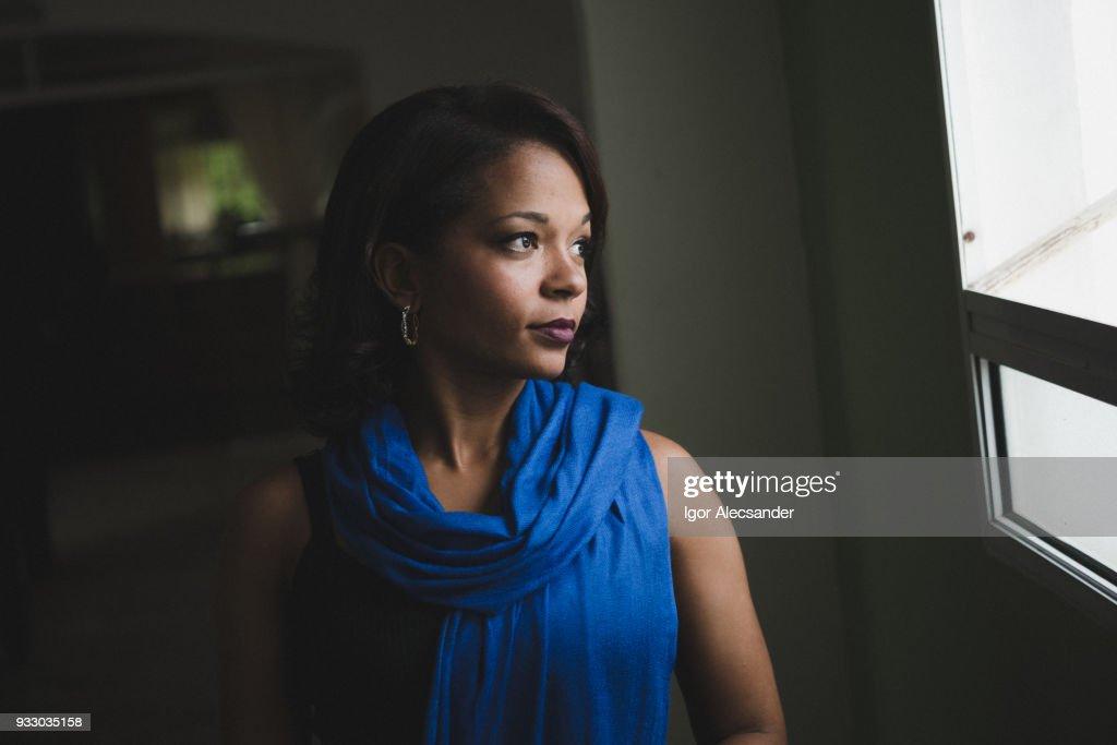 Mulher séria olhando para fora da janela de casa : Foto de stock