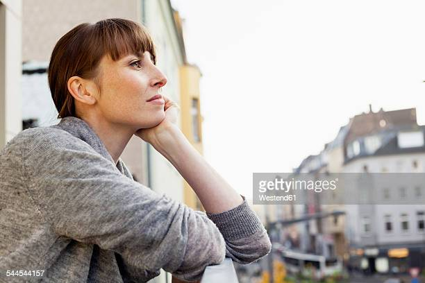 Serious woman on balcony thinking