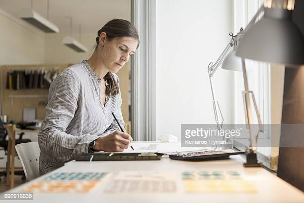 Serious woman painting while sitting at table in creative office