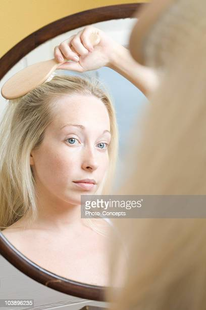 Serious woman peering into mirror looking at her reflection and brushing hair with hairbrush