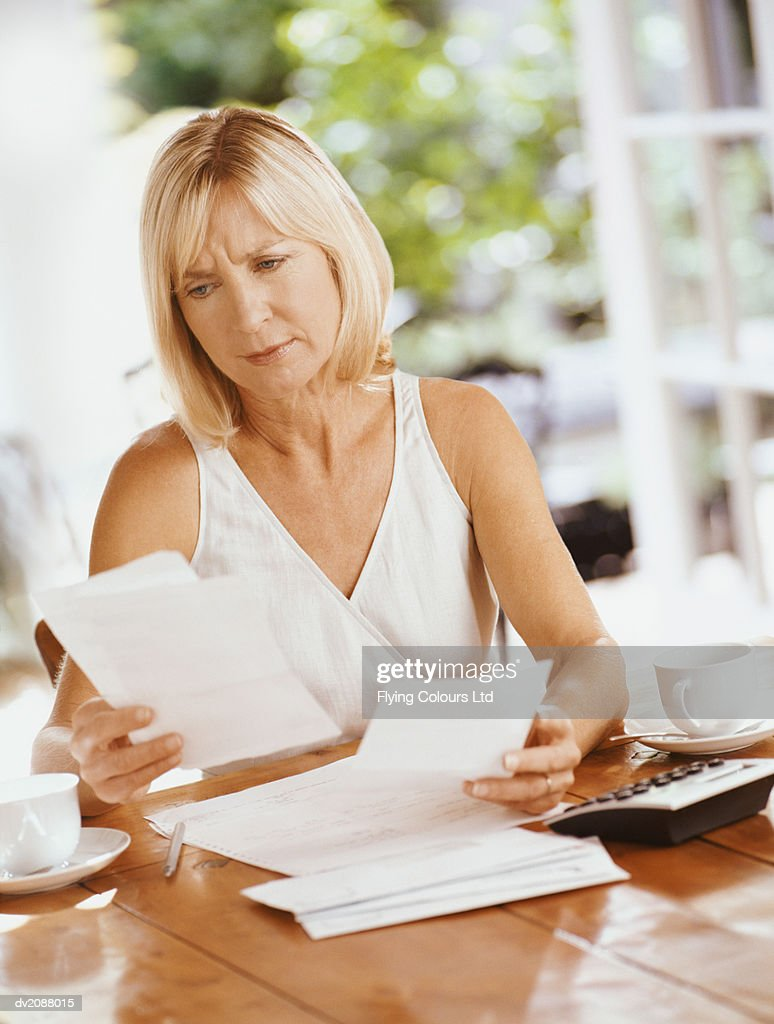 Serious Woman Sitting at a Table Indoors Reading Bills : Stock Photo