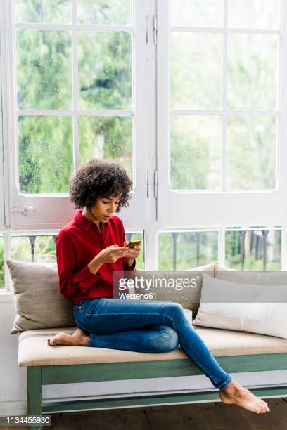 serious woman sitting at the window at home using cell phone - black blouse stock pictures, royalty-free photos & images