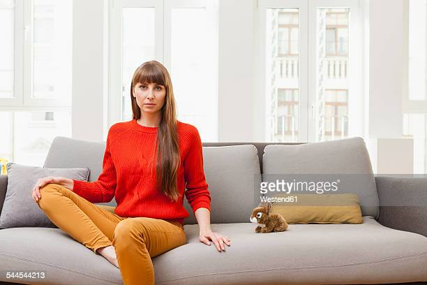 Serious woman sitting on sofa next to cuddly toy