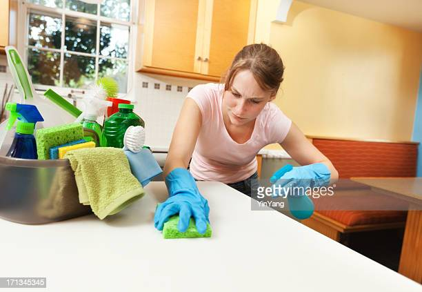 Serious Woman Spring Cleaning Kitchen Counter with Cleanser and sponge