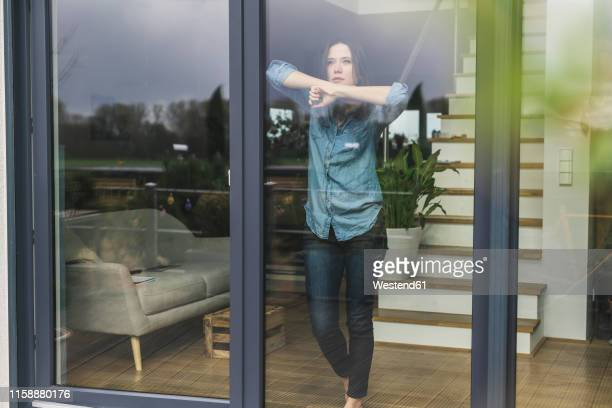 serious woman standing behind terrace door at home - looking at view - fotografias e filmes do acervo