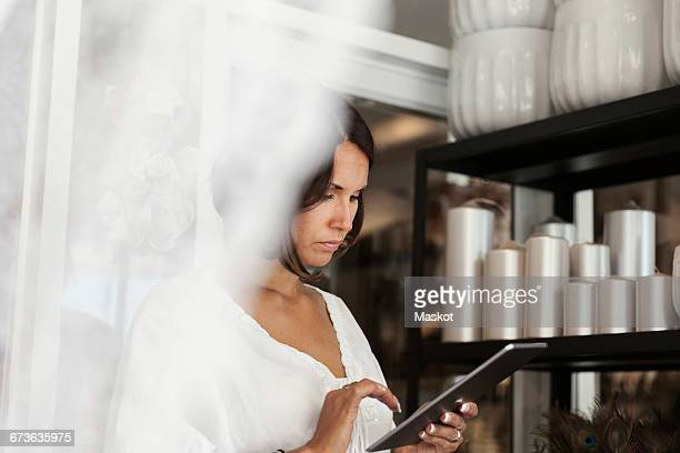 Serious woman using digital tablet while standing by candles on shelf at store