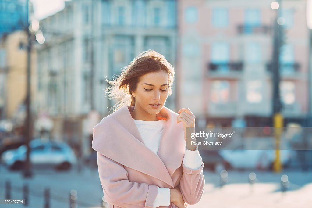 Serious woman walking outdoors on a cold sunny day : Photo