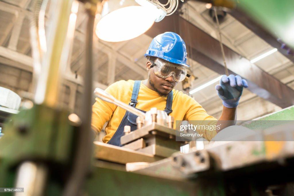 Serious worker repairing manufacturing machine : Stock Photo