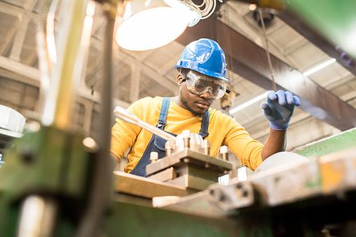 Serious worker repairing manufacturing machine 979414632