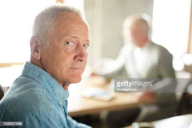 serious wrinkled handsome mature man with gray hair sitting in cafe and looking at camera - working seniors stock pictures, royalty-free photos & images