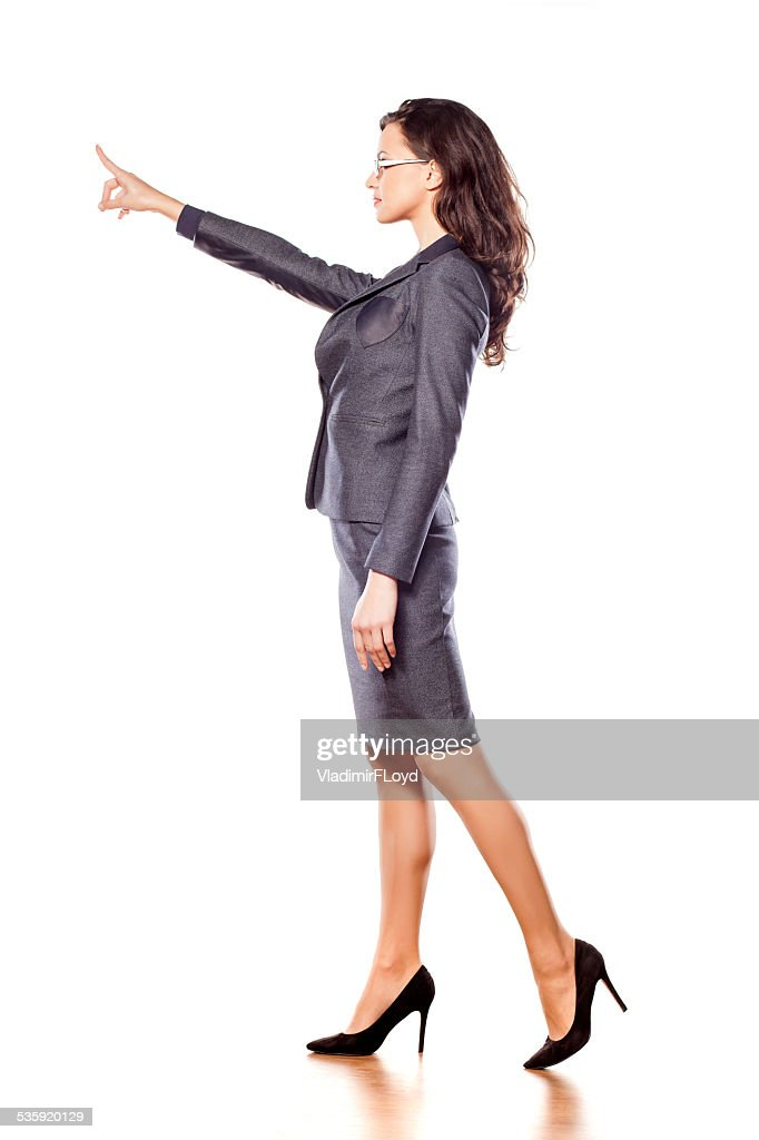Serious young beautiful business woman pointing at blank : Stock Photo