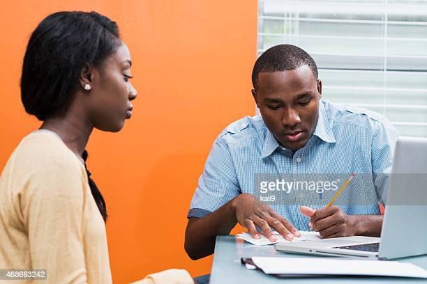 Serious young black couple working on home finances