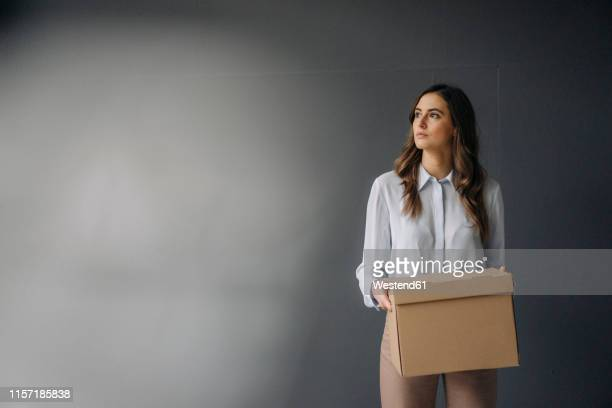 serious young businesswoman holding cardboard box - downsizing unemployment stock pictures, royalty-free photos & images