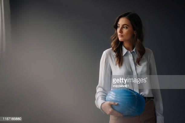 serious young businesswoman holding hard hat - só adultos imagens e fotografias de stock