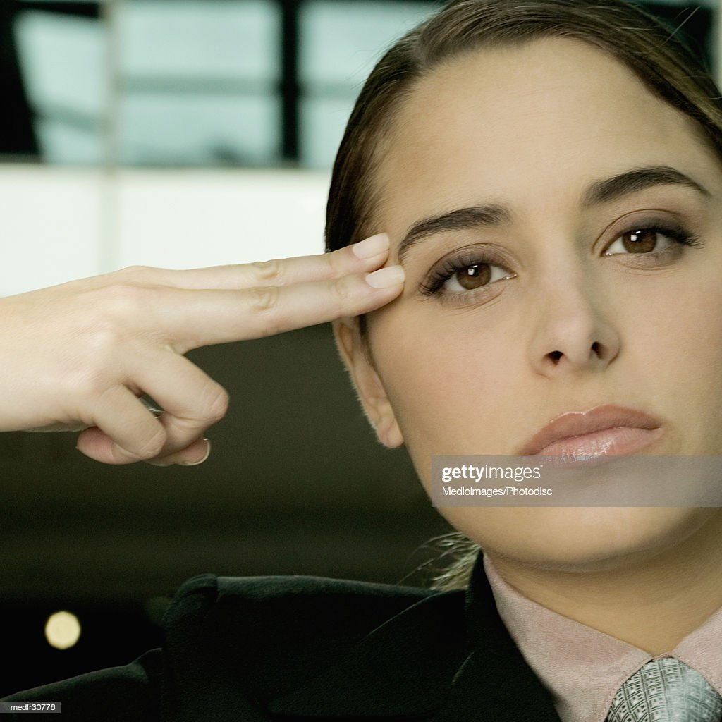 Serious young businesswoman holding two fingers against side of face, close-up : Stock Photo