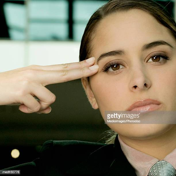 Serious young businesswoman holding two fingers against side of face, close-up