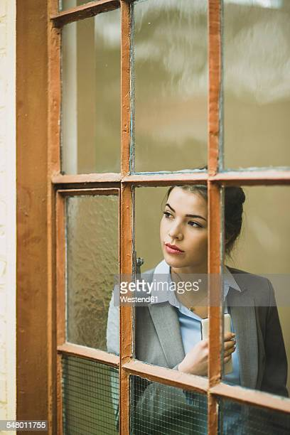 Serious young businesswoman looking out of window